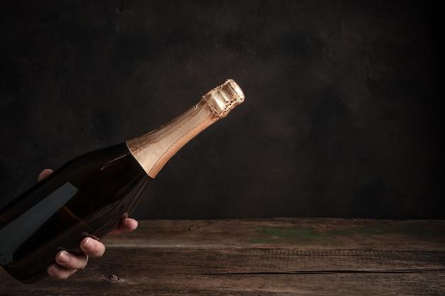 Una bottiglia di champagne senza etichetta nella mano di una donna