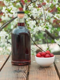 Una bottiglia di liquore alla ciliegia e bacche di ciliegia congelate di un albero in fiore. alcool fatto in casa a base di bacche di ciliegia.
