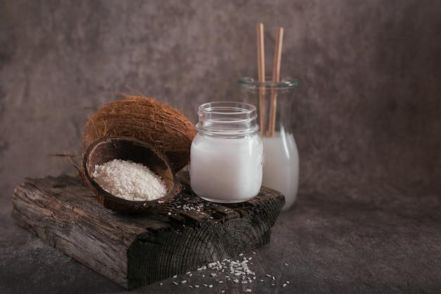 Bottiglia di latte vegano di cocco, olio di cocco, cocco intero e fiocchi su sfondo scuro. mangiare pulito e concetto di cibo sano.