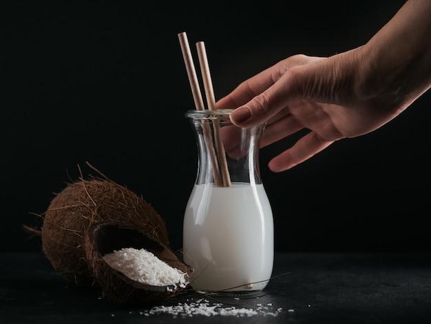 Bottiglia di latte vegano al cocco con cannucce, cocco intero e fiocchi su fondo nero
