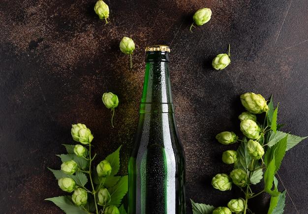 Bottiglia di birra fredda su sfondo grunge con luppoli verdi