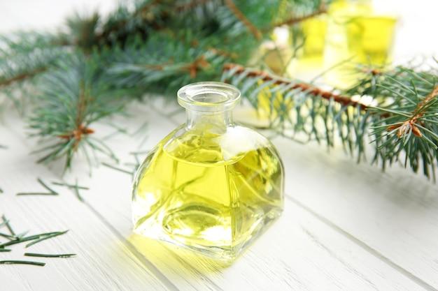 Bottiglia di olio essenziale di conifere e rami su sfondo di legno, vista ravvicinata