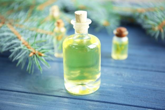 Bottiglia di olio essenziale di conifere e rami su fondo di legno