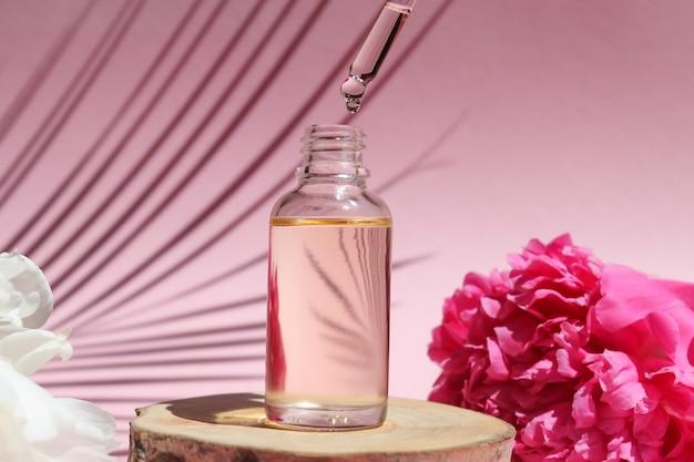 Bottiglia di olio essenziale cosmetico con contagocce su un olio di siero tagliato in legno gocciola dal contagocce