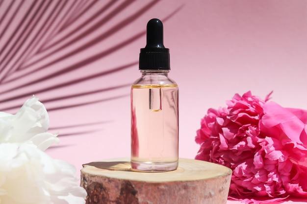 Bottiglia di olio essenziale cosmetico con contagocce su legno tagliato con fiori di peonia e ombra di foglie di palma