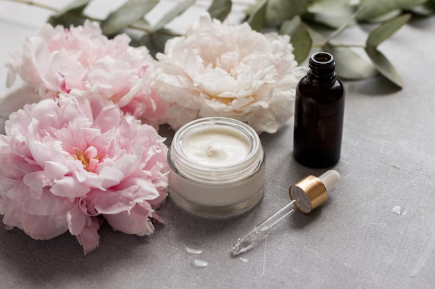Bottiglia di siero cosmetico con una pipetta e una crema idratante viso su uno sfondo di delicati fiori ed erbe. cura del viso per la donna.