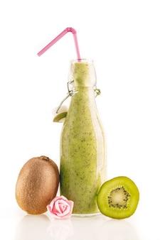 Bottiglia di delizioso frullato di kiwi verde con fette di kiwi e un piccolo fiore isolato su sfondo bianco. concetto di cibo sano, disintossicante e dietetico.