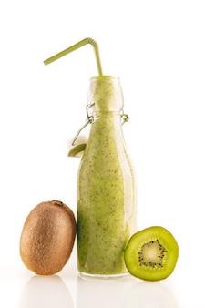 Bottiglia di delizioso frullato di kiwi verde con una cannuccia e fette di kiwi isolate su sfondo bianco. concetto di cibo sano, disintossicante e dietetico.