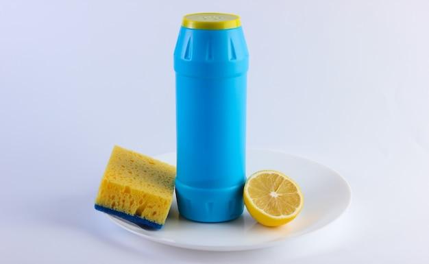 Bottiglia di detersivo e limone, spugna nel piatto. concetto di piatti di lavaggio