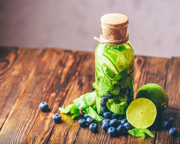 Bottiglia di acqua detox infusa con lime, menta e mirtillo e ingredienti sul tavolo. copia spazio a sinistra. veduta dall'alto.