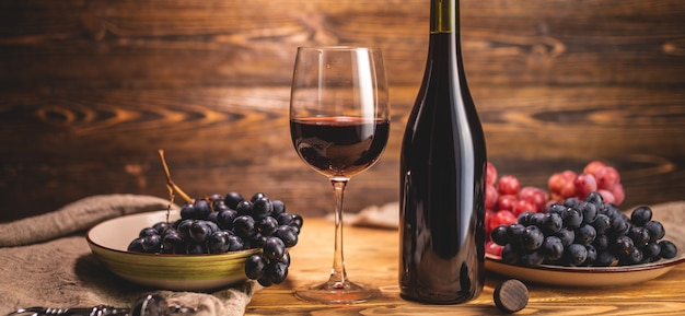 Una bottiglia di vino rosso secco con un bicchiere e un grappolo d'uva su un tavolo di legno