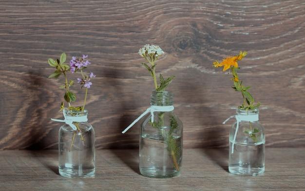 Una bottiglia di olio essenziale con erbe aromatiche, prezzemolo, timo, aneto, issopo, impostata su un vecchio sfondo di legno. cucina, medicina alternativa, massaggi, concetto di aromaterapia.