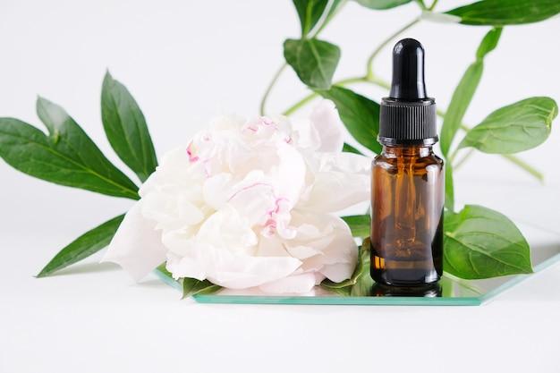 Bottiglia di olio essenziale con fiori bianchi