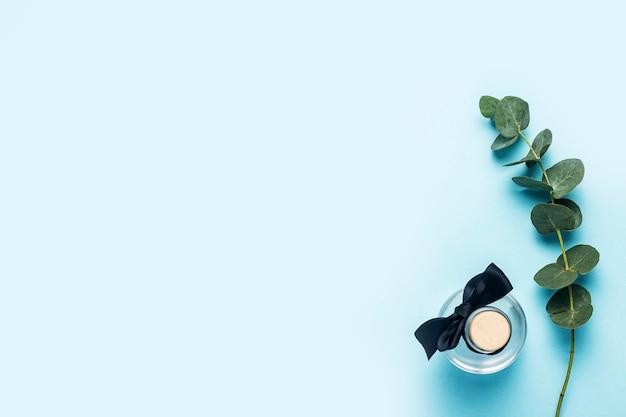 Bottiglia di olio essenziale di eucalipto, ramo di eucalipto verde su sfondo blu. vista dall'alto, piatto.