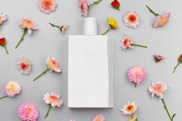 Bottiglia di profumo circondata da boccioli di fiori