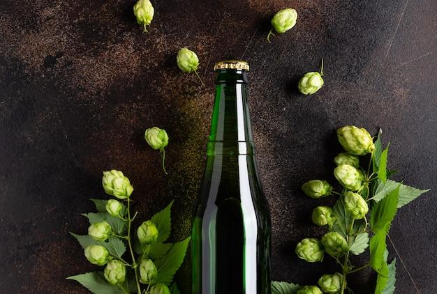 Bottiglia di birra fresca sulla tavola di lerciume con il concetto della fabbrica di birra del luppolo verde
