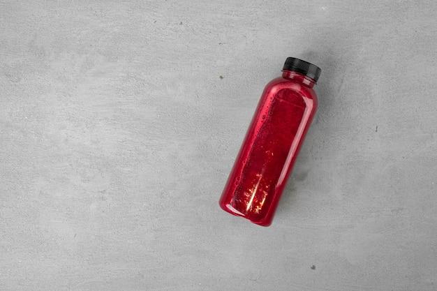 Bottiglia di succo di barbabietola fresca su sfondo grigio vicino