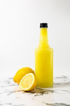 Bottiglia di limoncello fresco su piatto bianco su tavola di marmo