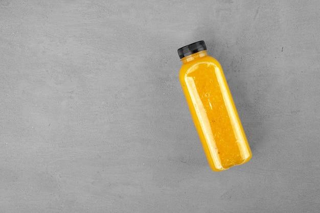 Bottiglia di succo d'arancia appena spremuto su sfondo grigio