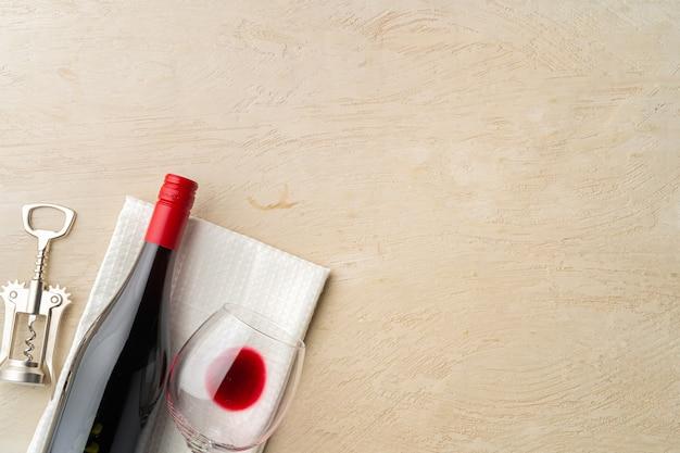 Bottiglia e bicchiere di vino rosso piatto giacevano sul grigio