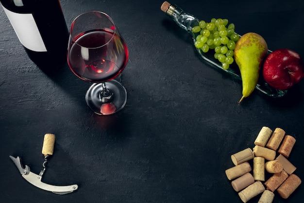 Una bottiglia e un bicchiere di vino rosso con frutta su sfondo di pietra scura