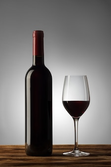 Bottiglia e bicchiere di vino rosso con una leggera sfumatura sullo sfondo