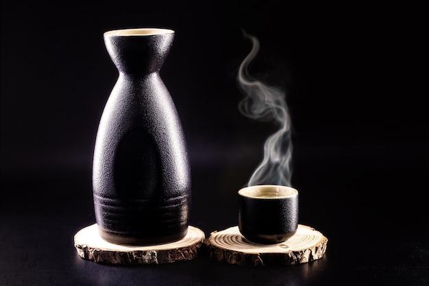 Bottiglia e bicchiere di sake, bevanda alcolica giapponese calda, con vapore, sfondo nero e spazio di copia
