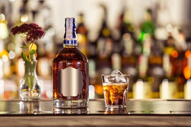 Bottiglia e un bicchiere di whisky sulla barra (primo piano). bevanda tradizionalmente irlandese