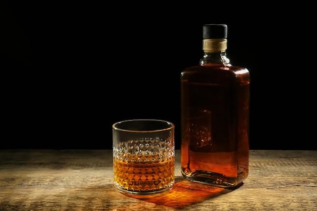 Bottiglia e bicchiere di whisky sulla tavola di legno contro il buio