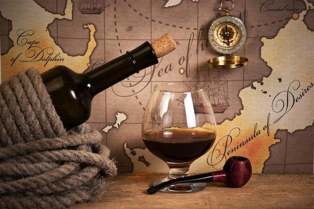Bottiglia e bicchiere di vino sullo sfondo di vecchie mappe
