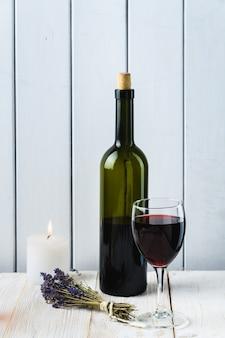 Bottiglia e bicchiere di vino su uno sfondo di legno bianco. stile rustico.