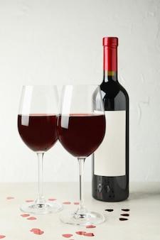 Bottiglia e bicchieri di vino rosso sulla tabella strutturata bianca