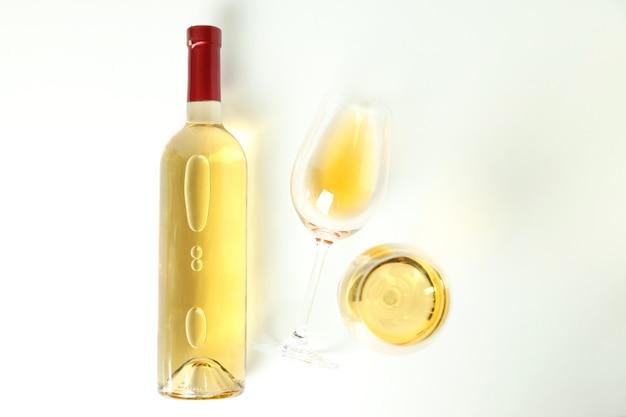 Bottiglia e bicchieri di vino su sfondo bianco
