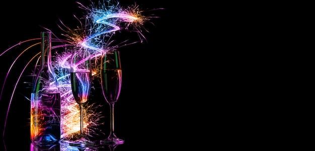Bottiglia e bicchieri con champagne alla luce del bengala colorato