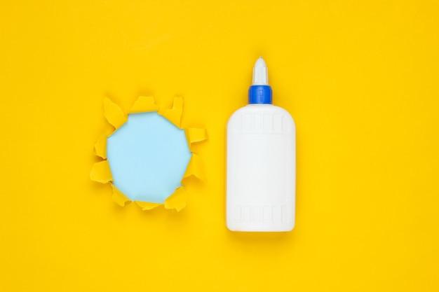 Bottiglia di colla su carta gialla con foro strappato