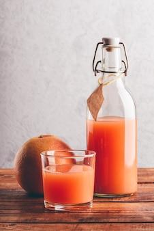 Bottiglia di succo di pompelmo con vetro e frutta sulla superficie in legno