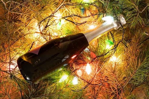 Una bottiglia di champagne verde avvolta in una ghirlanda luminosa come un albero di natale. anno nuovo concetto su sfondo naturale. copia spazio per il design della bottiglia