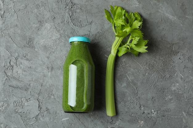 Bottiglia di frullato verde e sedano su sfondo grigio