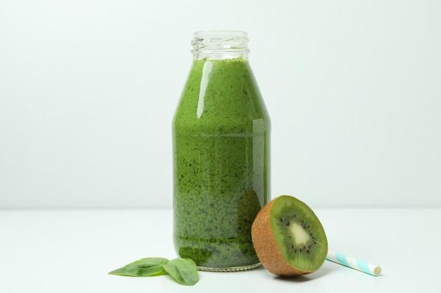 Bottiglia di frullato verde, kiwi, foglia di basilico e paglia sul tavolo bianco
