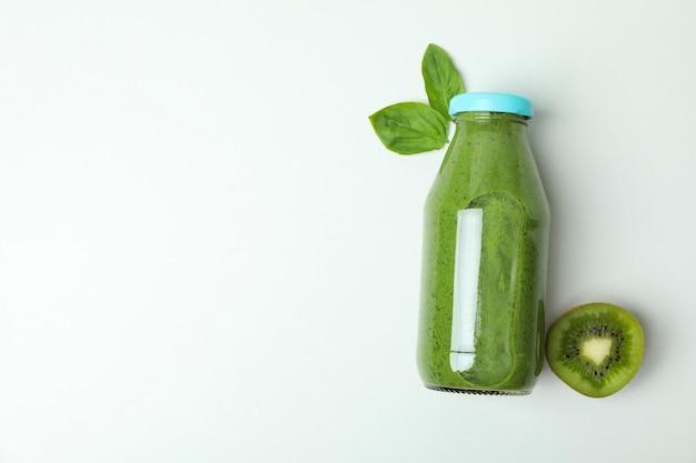 Bottiglia di frullato verde, kiwi e foglia di basilico su sfondo bianco