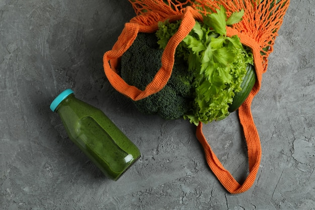 Bottiglia di frullato verde e borsa di paglia con ingredienti su sfondo grigio con texture