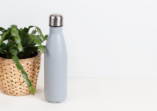 Bottiglia sulla scrivania grigia circondata da gadget moderni e piante
