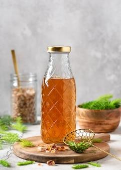 Bottiglia di sciroppo fatto in casa a base di giovani punte di abete e zucchero naturale sul tagliere di legno
