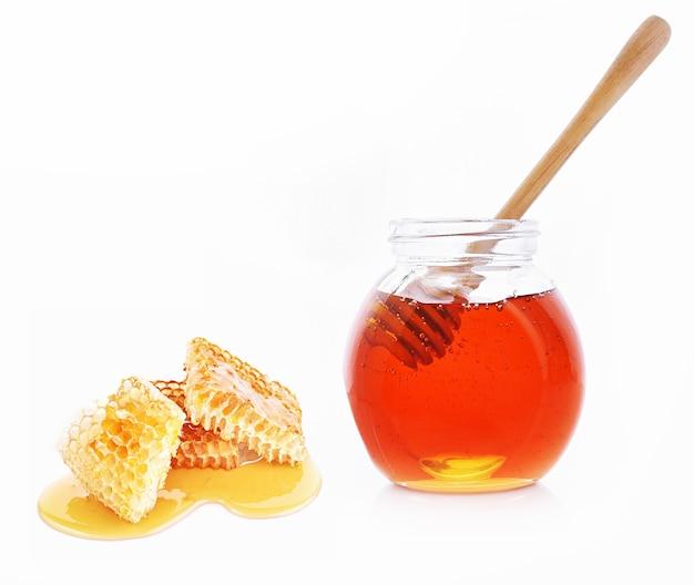 Bottiglia di miele, cucchiaio e favo su sfondo bianco