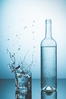 Bottiglia di acqua ghiacciata con gocce e bicchiere d'acqua con ghiaccio che cade con spruzzi