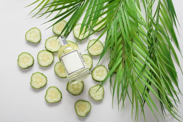 La bottiglia è su cerchi di cetriolo, su uno spazio bianco, vista dall'alto, il cetriolo è sparso in tutto lo spazio. concetto di olio per il corpo naturale