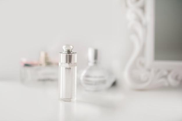 La bottiglia è sul comò nella camera da letto bianca. profumo in un interno luminoso.