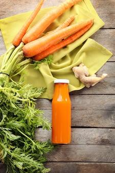 Bottiglia di succo di frutta con carote fresche su sfondo di legno