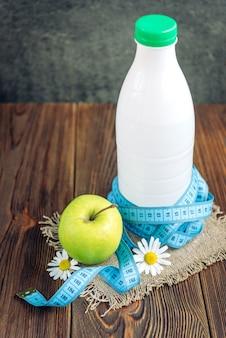 Bottiglia di kefir, mela verde e metro a nastro su legno scuro