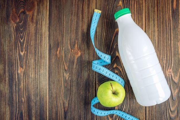 Bottiglia di kefir, mela verde e misura di nastro su fondo di legno scuro. dieta e concetto sottile.